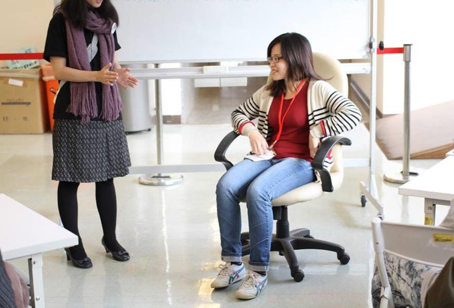 模擬輪椅使用者的體驗者正坐在有輪子及扶手的椅子上