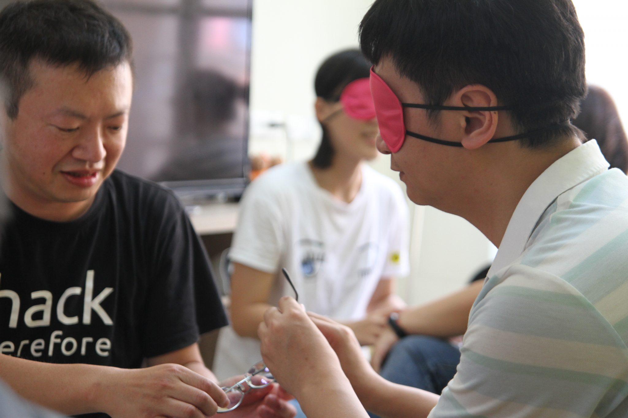 戴著眼罩的學員正在用非視覺的方式觀察另一位學員