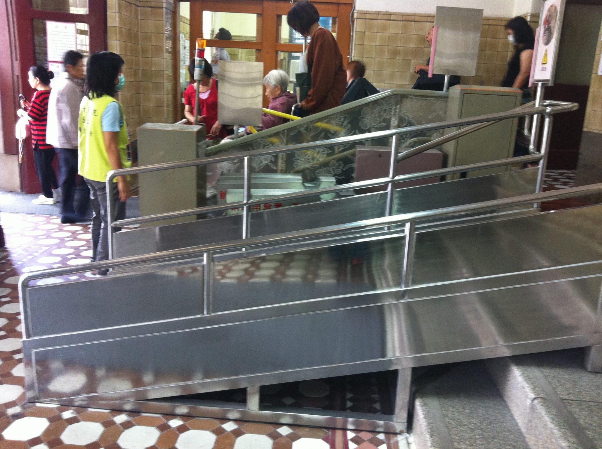 醫院門口有輪椅使用者正經過斜坡